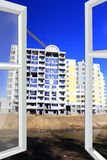 Opened window to multistorey house and crane Royalty Free Stock Photo