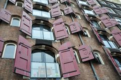Opened windows of canal houses with red shutters, Amsterdam, Netherlands