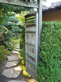 Open gate and a stone path. Opened wooden gate with a view of a traditional Japanese style garden with a stone path Royalty Free Stock Photography