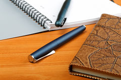 The opened writing-book in a leather cover. And  pen Stock Images