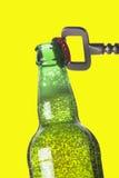 Opening beer bottle with metal opener Stock Photos