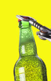 Opening beer bottle with metal opener Royalty Free Stock Photos