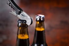 Opening beer bottle with metal opener. Food and beverages concept Royalty Free Stock Images