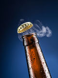 Opening of beer cap with the gas output. Condensated drops on the bottle Stock Image