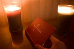 Opening bible. Photo of a hand opening the book of common prayer (a collection of traditional Christian Anglican liturgy) lit by candles Stock Image