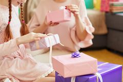 Opening Birthday Gifts Close up. Close up of cute little girl wearing pink opening Birthday presents at party, copy space royalty free stock photography