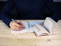 Opening book and taking note. Study on wood table Royalty Free Stock Photo