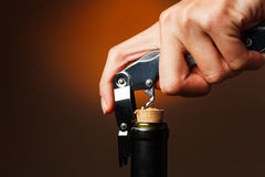 Opening of bottle of wine with corkscrew Stock Photos