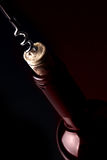 Opening a bottle of wine, on dark background. Red reflection. Stock Image