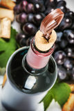 Opening a bottle of wine and grapes Royalty Free Stock Image