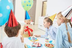 Opening box with gift. Little boy opening giftbox and looking at birthday present inside during celebration with his friends Royalty Free Stock Photos