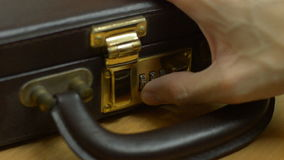 Opening briefcase. Unlocking and opening briefcase stock footage