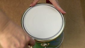 Opening A Can Of Paint. Taking the lid off a can of paint with a screwdriver then stirring with a wooden spoon stock video footage