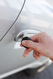 Opening car door. A hand opening a car door with a key Royalty Free Stock Images