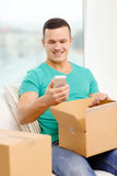 Opening cardboard box and taking out smartphone Royalty Free Stock Photos