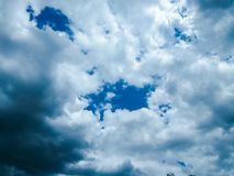 Opening In The Blue Cloudy Sky. Opening in the center of a dramatic cloudscape Royalty Free Stock Photos