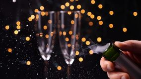 Opening champagne bottle closeup. Sparkling Wine over Holiday Bokeh Background. Slow motion