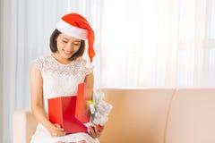 Opening Christmas gift. Happy Vietnamese woman opening Christmas gift Royalty Free Stock Photos