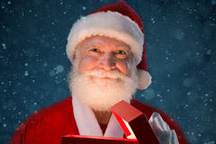 Opening Christmas present. Portrait of Santa Claus opening Christmas present Stock Photo