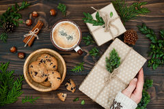 Opening Christmas present. Woman's hands holding decorated gift box on rustic wooden table. Ideal morning breakfast. Royalty Free Stock Photos