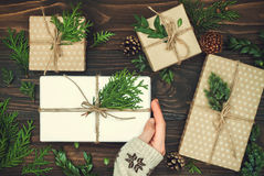 Opening Christmas present. Woman's hands holding decorated gift box on rustic wooden table. Christmas or New year DIY packing. Overhead, flat lay, top view Stock Photo