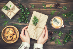 Opening Christmas present. Womans hands holding decorated gift box on rustic wooden table. Overhead, flat lay, top view royalty free stock photo