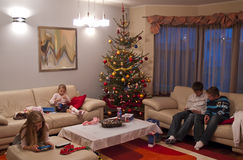 Opening Christmas presents. Four children (boys and girls) playing with their new Christmas presents at home Royalty Free Stock Image
