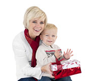 Opening Christmas Presents. A cute little boy opening christmas presents with his mother. Isolated on a white background Royalty Free Stock Image