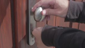 Opening and closing the door. Close up of a hand opening and closing a wooden door with keys
