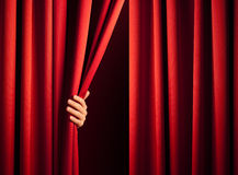 Opening the curtain. Male hand in the act of disclose the scene shifting the red curtain Royalty Free Stock Photos