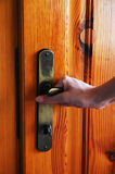 Opening door. Hand opening the wooden door Stock Images
