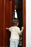 Opening the door. A cute chinese baby is opening the door in home Stock Photo