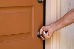 Opening Door. Man opening the front door of his home Royalty Free Stock Photos