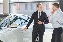 Opening a door. Car salesperson is opening a door of the car royalty free stock photos