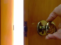 Opening a Door to Light. Close-up of a hand reaching for a doorknob and opening the door to reveal a bright light beyond Stock Image