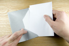 Opening envelope with fingers crossed Royalty Free Stock Images