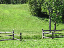 Opening in fence to a grass meadow. Stock Images