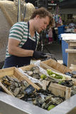 Opening fresh oysters at the market Royalty Free Stock Image