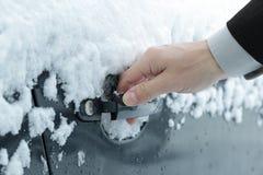 Opening a frozen car door Stock Images