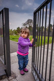 Opening the gates. Little girl opening metal gates leading to the playground Stock Images