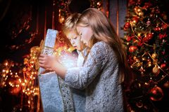 Opening gift together. A portrait of children opening a gift box. Merry Christmas, happy New Year. Luxurious apartment with a christmas tree, lights and stock image