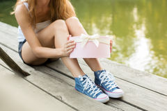 Opening a gift on a wooden location Royalty Free Stock Images