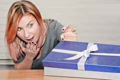 Opening gift. Young woman surprised at opening gift royalty free stock photo