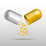 Opening gold medical capsule Royalty Free Stock Image