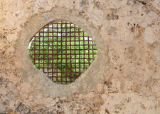 Opening with grid in old stone wall Royalty Free Stock Images