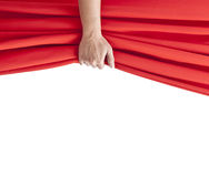 Opening. Hand opening red curtain on white Royalty Free Stock Photography