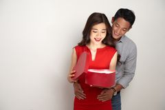 Opening his gift. Happy young women opening heart shaped gift box from her boyfriend with Valentine present Stock Images