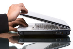 Opening laptop. Woman's hand open a laptop, shot against very bright white screen Royalty Free Stock Image
