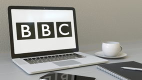 Opening laptop with British Broadcasting Corporation BBC logo on the screen. Modern workplace conceptual editorial 4K. Animation royalty free illustration