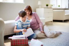 Opening letters. Portrait of cute boy opening envelope with his mother near by at home Stock Images
